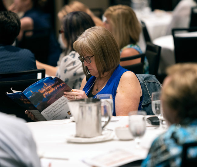 Woman in blue sleeveless shirt, reading program, at a table.