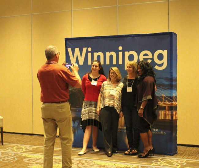 Man in orange shirt taking photo of four women in front of the Winnipeg poster at back of large room. A few shots later, the photo of the same four women.